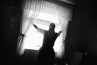 A Hutterite woman opens curtains in her home at the Springdale Hutterite Colony outside of White Sulphur Springs, Montana.  Hutterites are a traditional Anabaptist religious society with origins in Germany.