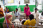 Family member gather around the patient in the pediatrics ward of Duncan Hospital in Raxaul of East Champaran district of Bihar, India. Since 2008 the Foundation and Geneva Global have been investing in the training of medical staff to improve the lives of people living in 600+ villages in the region. The NGOs are delivering cost effective interventions to address treatment, care and prevention of diseases, disability and preventable deaths amongst infants, adolescent girls and women of child-bearing age. There is statistical and anecdotal evidence that there have been vast improvements and a total of 40-50% increased immunization for all children under 6 has meant that communities can be serviced and educated long term. Photograph: Sanjit Das/Panos for Legatum Foundation