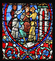 2 courtesans surround the younger son, 1 crowns him with a wreath of flowers while the other kisses him, from the Parable of the Prodigal Son stained glass window, in the north transept of Chartres Cathedral, Eure-et-Loir, France. This window follows the parable as told by St Luke in his gospel. It is thought to have been donated by courtesans, who feature in 11 of the 30 sections. Chartres cathedral was built 1194-1250 and is a fine example of Gothic architecture. Most of its windows date from 1205-40 although a few earlier 12th century examples are also intact. It was declared a UNESCO World Heritage Site in 1979. Picture by Manuel Cohen