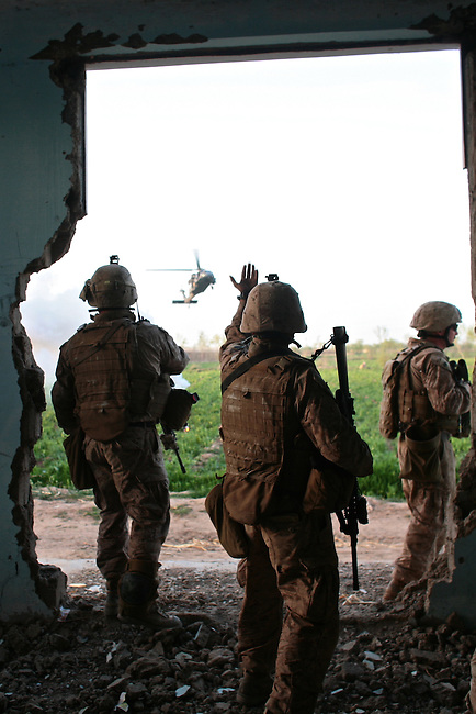 Marines from Company L,  3rd Battalion, 6th Marine Regiment wave in a medevac helicopter to pick up Lance Cpl. Matthew W. McElhinney, who has been shot in the back during a gun battle with Taliban fighters near Marjah, Afghanistan. March 10, 2010. DREW BROWN/STARS AND STRIPES
