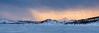 Winter snow flurries passing over lake Ostadvatnet, Vestvågøy, Lofoten Islands, Norway
