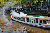 Amsterdam, Holland. Steamboat pleasure craft heading down a canal.