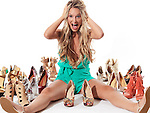 Young woman can't find a pair of matching shoes, witting on the floor screaming surrounded by several pairs of different fashionable shoes isolated on white background. Humorous concept.