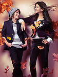 Smiling boy and a teenage girl in fashionable clothes standing under falling red autumn leaves artistic fall fashion photo