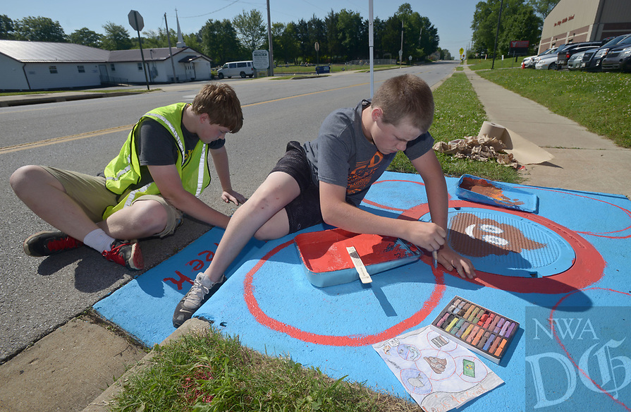 NWA Democrat-Gazette/BEN GOFF @NWABENGOFF<br /> Wesley Ewald (left) and Randy Cook, Pea Ridge Middle School 8th graders, paint their design on a storm drain Monday, May 15, 2017 along Weston Street in front of the school in Pea Ridge. Students in the school's 8th grade elective art class partnered with UpStream Art to learn about water quality issues before working in small groups to designs and paint murals on six storm drains near the school.
