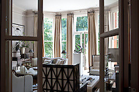 View through the open French doors into the spacious living room with floor-to-ceiling windows