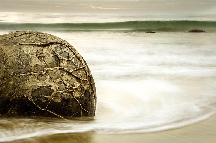 Moeraki Boulder surrounded by waves, coastal Otago. <br /> <br /> South Island, New Zealand - stock photo, canvas, fine art print