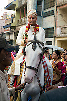 The groom Soni begins the Baraat (Hindi for marriage procession) by mounting a white horse and leading the wedding guests through town toward the reception hall on Jan. 5, 2008. The groom and his horse lead the way while the ?baraatis,? the people accompanying the procession, dance and sing.