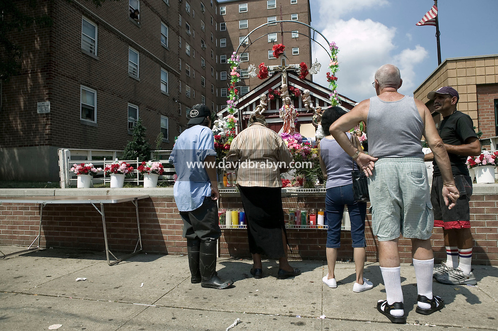 People gather in front of a statue of Christ that rests in a small shrine on Jackson and Third streets in Hoboken, NJ, USA, to examine the eye that is said to have suddenly opened without human intervention a few days earlier in what locals believe is a sign from God, 31 July 2005. Photo Credit: David Brabyn