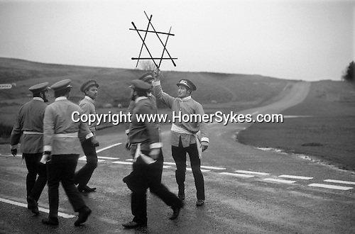 Goathland Plough Stots. Goathland Yorkshire UK  Sword Dance Team 1972.<br /> <br /> This interesting custom would not exist if it had not been revived by F. W. Dowson in 1923 after a lapse of nearly sixty years. Apart from a break in the second world war, the custom has carried on since then. The traditional date for its performance was plough Monday, or first Monday after Twelfth Night (6 January), which by tradition was the first day of the agricultural labourers&rsquo; week&rsquo;s holiday. However, after 1947 this day was changed to the first Saturday after plough Monday. In northern Middle English 'stot' meant a bullock, but the word has been transferred to the youths who drag a bullock about in the Plough Monday procession. According to the traditional custom this was led by a 'Lord' and 'Lady' followed by a group of men in disguise, known as 'Toms', who made a collection. Next came the sword-dancers and musicians and taking up the rear<br /> were the plough stots, with 'Betty' carrying a broom, and 'Old Isaac' collecting alms. The whole procession could number as many as forty people. During the week's holiday they first toured their own village and then the ones near by, especially those that had no team. At various places in each village the sword-dancers performed and a collection was made. Donations were expected and if they were not forthcoming the farmer ran the risk of having his lawn ploughed up. At the end of the week it was the custom to hold a festival and dance, to which the women folk were invited. Expenses were met out of the funds collected during the week and the remaining money divided up between the performers.