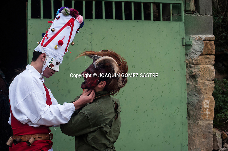 A white Danzarin (another character carnival Vijanera) helps another participant to tie the mask.