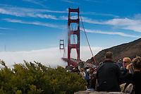 People enjoy Golden Gate Bridge in a fog from Horseshoe bay vista point, San Francisco