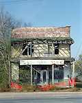 the old Bryant Store in Money, MS. from 11/27.02.The old Bryant store is just over his shoulder, it has stood the test of time but is in bad shape and decaying. The store is where Emmett Till a young black man from chicago who stopped in the store and whistled or cat called at the oweners blonde and white wife,Emmett was later found lynched and the men who were accused of the crime were found not guilty.The store owners was Roy Bryant it was his wife that was whistled at and Roy owned the store with his half brother J.W.Milam in 1955. Bryant and Milam were indicted for kidnapping and lynching Till but were later acquited of all charges.(photo/Suzi Altman)