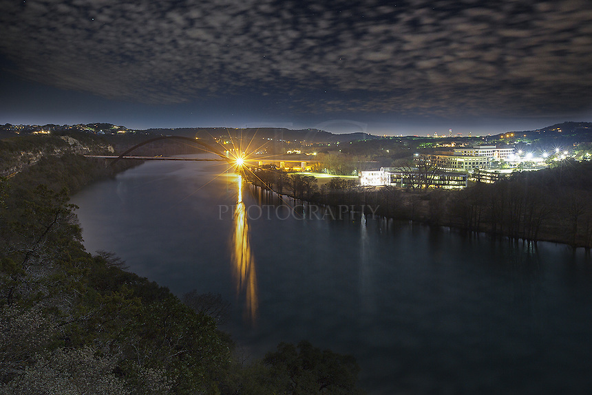 Lit by full moon, the 360 Bridge and Colorado River Valley shine in the dark hours of the night. Overhead, patchy clouds slide across the sky. In the distance is the sleeping Austin skyline, highlighted by the Austonian and iconic Frost Tower.