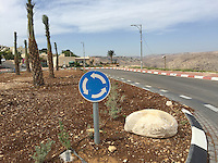 14. &quot;Roundabout&quot;: median and highway, Nofei Prat, West Bank.<br /> <br /> The bright blue &quot;roundabout&quot; sign seems like a metaphor for the ongoing land disputes in the West Bank. Many settlers use the biblical terms, &quot;Judea and Samaria,&quot; to refer to the area in place of &quot;West Bank.&quot; Does this help justify their presence and their actions? On the left one can see the settlers' homes; on the right the Judean Desert hills and another settlement in the distance. And in the middle, the blue sign and a heavy rock are firmly planted, as if to say, &quot;We're not going anywhere!&quot;