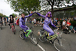 A pair of purple painted bicycle riders bump fists while peddling in the 21st Annual Fremont Summer Solstice Parade in Seattle on June 20, 2009. The parade was held Saturday, bringing out painted and naked bicyclists, bands, belly dancers and floats. (Jim Bryant Photo © 2009)