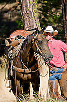 Western California cowboy wearing a red striped shirt, taking a break, standing next to his chestnut horse, with one stirrup thrown over saddle, standing in grassy meadow near pine trees in the California Sierras.
