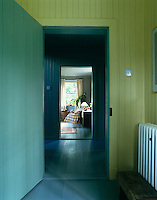 Tongue-and-groove panelling painted in green, yellow and blue with a painted wooden floor in this view from the kitchen looking into the sitting room
