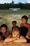 YANOMAMI TRADITIONAL LIFESTYLES , Amazon, near Boavista, northern Brazil, South America. Yanomami children with airplane behind on small airstrip near their home deep in the rainforest. Ecological biosphere and fragile ecosystem where flora and fauna, and native lifestyles are threatened by progress and development. The rainforest is home to many plants and animals who are endangered or facing extinction. This region is home to indigenous primitive and tribal peoples including the Yanomami and Macuxi.