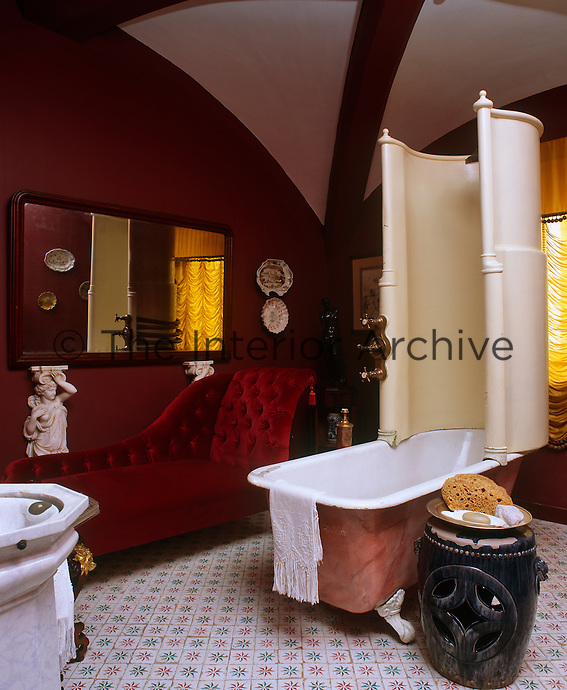 A deep red velvet chaise-longue sits beneath the mirror in this bathroom furnished with a roll-top bath with a Victorian shower