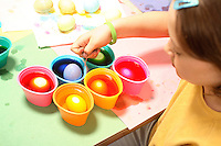 Photo of a young girl coloring Easter eggs with several cups of eggs in different, brightly colored dye.