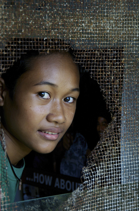 STUDENTS IN THE PUBLIC HIGH SCHOOL CHUUK, MICRONESIA, PACIFIC,THE LOOK THROUGH A BROKEN CLASSROOM WINDOW
