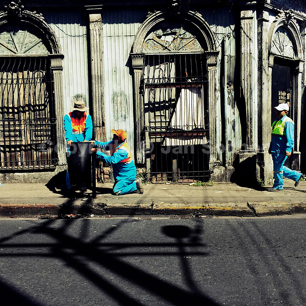 Salvadoran garbage collectors work in front of a ruined house, designed by using bold Spanish colonial architecture elements, built in the center of San Salvador, El Salvador, 10 November 2016.