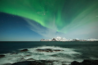 Northern lights fill sky over sea, Flakstadøy, Lofoten Islands, Norway