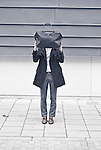 A man standing on a street hiding behind a bag