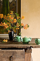 On a rustic sideboard in the kitchen a jade-green tea service and a simple jug of orange flowers create a perfect still-life