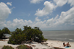 Couple sit along the shore of Annie's Beach in the Florida Keys