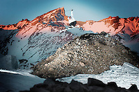 JF Cusson, freeskiing pioneer, 180 over a big pile of rocks, avalanche barrier in las lenas, argentina, sunset and mountain range in the backround