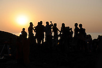 Silhouette of group of people dancing at sunset near the sea