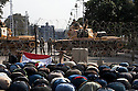 Egyptian anti-government protesters pray in the street outside the heavily guarded Orouba Presidential Palace February 11, 2011 in the Heliopolis district of Cairo, Egypt. Protesters marched Friday on a number of public buildings including the palace in an effort to spread their ongoing protests that are now in their 18th day. (Photo by Scott Nelson)
