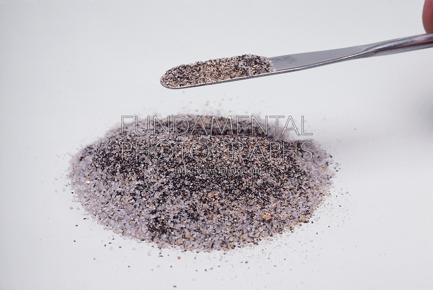 MAGNET ATTRACTS IRON FILINGS MIXED IN SAND (2 of 3)<br /> Compound Is Mixed<br /> A compound mixture of  iron filings, gold dust, sugar, and sand is mixed in preparation of magnetism experiment. The iron filings (ferromagnetic substance) are separated from the mixture by the field of the magnet.