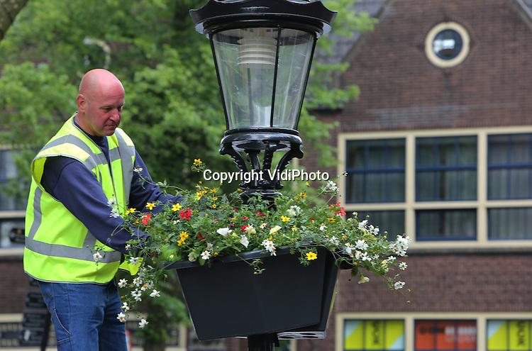 Foto: VidiPhoto<br /> <br /> UTRECHT - Medewerkers van Oase-Lease uit Leersum bevestigen dinsdag de laatsten van honderden bloeiende bloembakken aan lantaarnpalen bij het Domplein, langs het fietsparcours van de Tour de France die 4 juli in Utrecht van start gaat. In de komende weken groeien de hangbakken verder uit. De fleurige beplanting met onder meer Surfinia&rsquo;s, Geraniums en Bidens moet voor een gezellige zomersfeer zorgen zodat het publiek en de inwoners van Utrecht zich in het centrum en de wijken extra welkom voelen.  De kleuren van de zomerbloeiers, geel en wit met rode accenten, zijn in overleg met de gemeente Utrecht gekozen. Geel en wit verwijzen naar de Tour de France, rood is de kleur van de gemeente Utrecht. De hanging baskets blijven na de Tourstart gewoon hangen en bloeien tot diep in het najaar. Oase-Lease zorgt voor onderhoud en watergeven van de hangende tuintjes. De binnenstad van Utrecht wordt door het Leersumse bedrijf op dit moment tevens verrijkt met bloeiende gevelbakken en bloemenzuilen.