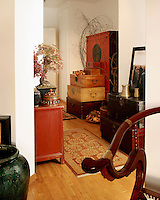 Lacquered antique Chinese chests are stacked in the entrance to the apartment, providing both practical storage and decoration