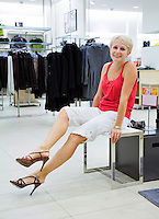 Woman with different high-heeled shoes in shop. Fashion, retail store, shopping.