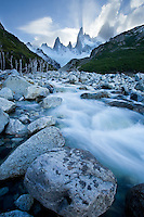 The peaks of Patagonia carve a shadow through the clouds as the sun sets near El Chalten, Argentina