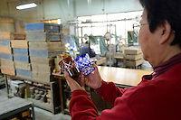 Shimizu Glass CEO, Michio Shimizu, holding a two Edokiriko glasses, Tokyo, Japan, January 14, 2015. Edokiriko is a style of cut glass that dates back to 1834 and is similar to British cut glass. It makes use coloured glass and highly-intricate Japanese motifs.