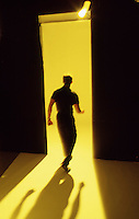 Man on yellow seamless walking away from camera