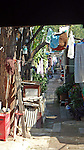 an alley in Beijing between traditional hutong homes, clothes hanginout to dry