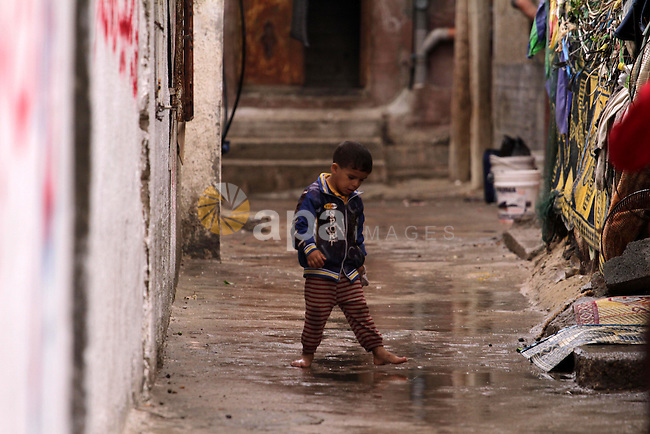 A Palestinian boy walks in a flooded street on an alley on a raining day at al-Shati refugee camp, the third largest in the Palestinian Territories, in Gaza City on October 30, 2013. Photo by Mohammed Asad