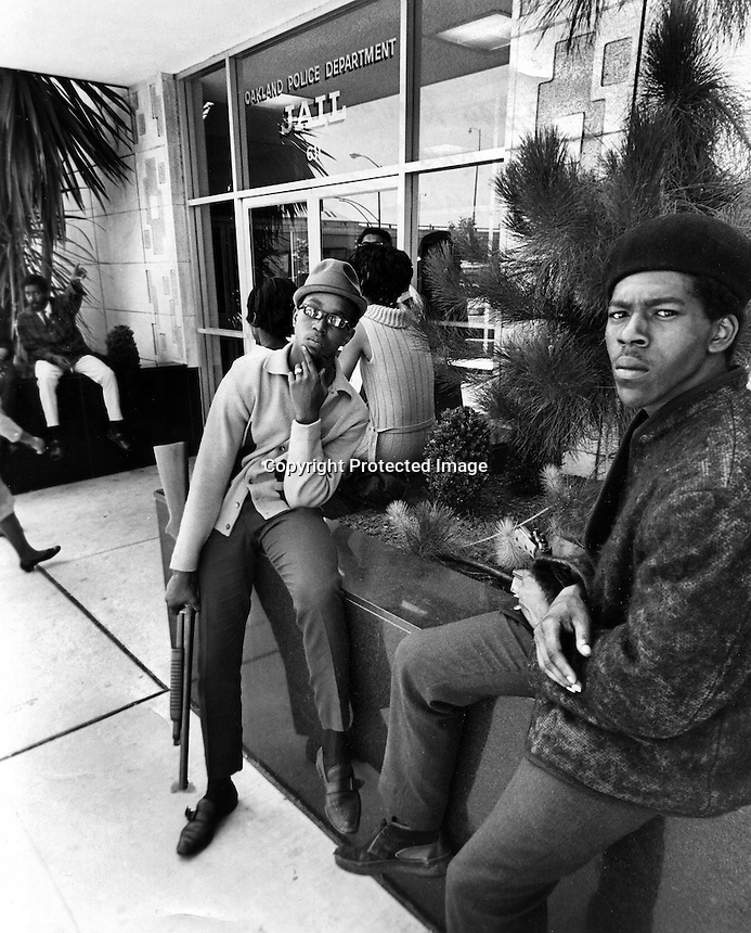 Black Panthers 17 yr-old Bobby Hutton (with shotgun) and Reginald Forte in front of the Oakland Police Dept. Jail protesting treatment by police. (1967 photo by Ron Riesterer)<br /> copyright @ 2014.