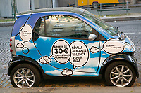 A Smart Car with advertising parked on the street in Paris, France
