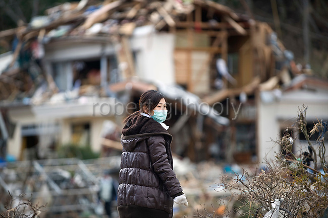 Mayumi Abe looks on at the wrecked remains of her family's home at Imeshi village on the Oshika Peninsula, Miyagi Prefecture, Japan on 19 March, 2011.  Photographer: Rob Gilhooly