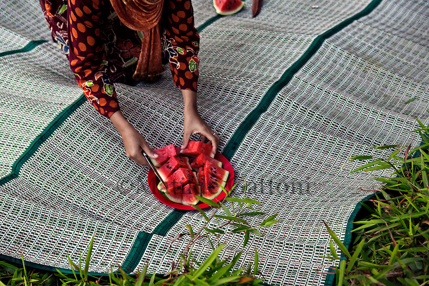 """Indonesia - Bangka Island - Rebo - A young mother serving watermelon to her family during a Friday supper. According to researches if lands are not properly reclamated the soild remains toxic and therefore vegetables and fruits which are grown will be radioactive. """"The impact of the destruction we are seeing now will last decades, if not centuries"""" he predicts. """"Some species of fauna are already disappearing, as well as some high quality wood forest plants. If action is not taken now, something really bad will happen to this land."""""""