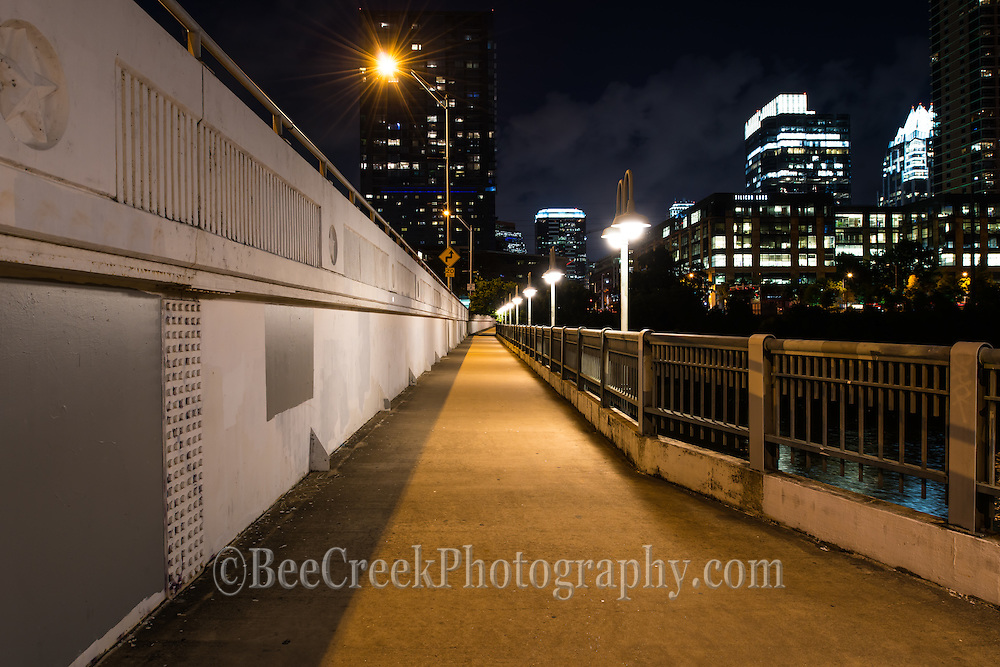 This is an image taken from the First Street Bridge in downtown Austin at night. We like the street scene with the city peaking up from behind.
