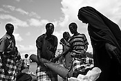 A group of refugees seen waiting outside a food distribution point in the IFO Camp of the Dadaab refugee camp in northeastern Kenya. Hundreds of thousands of refugees are fleeing lands in Somalia due to severe drought and arriving in what has become the world's largest refugee camp. Photo: Sanjit Das/Panos