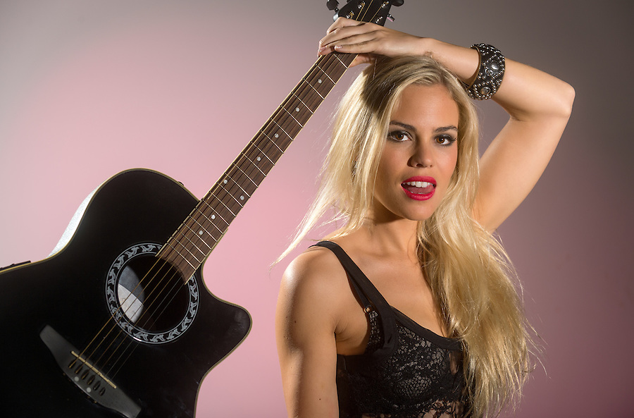 Sexy blonde rocker woman holding electric guitar